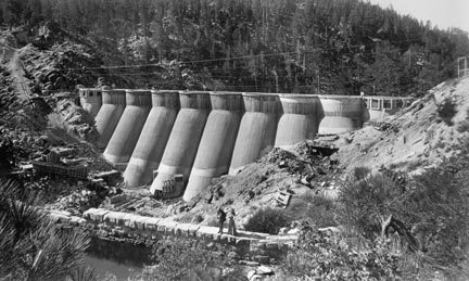 In 1912, a year after the previous photo was taken, the multi arch dam is finished. Notice the man and women standing on the old rock dam.