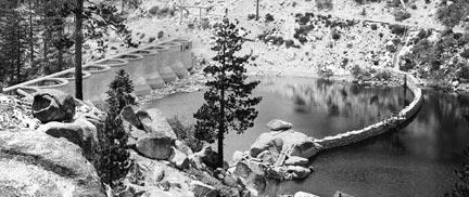 The flood gate on the old rock dam has been opened and the area between the dams is allowed to fill with water. The new dam is 20 feet higher than the old rock dam. When Big Bear Lake is full the rock dam will disappear from view.