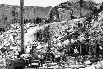 Workers are setting up a steam engine was set up on the valley floor to mix concrete. This engine and all the rest of the equipment and materials used in the dam's construction had to be hauled up by horse drawn wagon from Victorville.